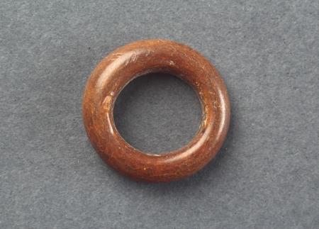 Obrączka szklana  Kółko szklane o barwie brązowej. Znaleziska tego typu są interpretowane jako pierścionki, często jednak wskazuje się też na ich inne funkcje, na przykład jako naszywek na odzież lub nawet jako paciorków różańca. Formowano je, owijając wokół metalowego pręta cienką nitkę szklaną, którą następnie rozgrzewano i odpowiednio obracając, nadawano pożądany kształt. Inny sposób polegał na nabraniu na koniec metalowego pręta niewielkiej ilości masy szklanej, którą przebijano, rozgrzewano, osadzając głębiej na trzonku, a następnie przez energiczny ruch obrotowy uzyskiwano obrączkę. Szklane kółeczka były znajdowane również na terenie szczecińskiego Podzamcza już w nawarstwieniach z 1. ćwierci XIII wieku.
