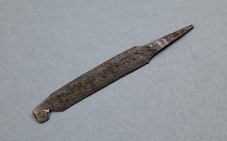 Nóż żelazny  Przednia część jego tylca (tylec do tępa część głowni noża – przeciwstawna do ostrza) jest skośnie ścięta, tylna prosta, a trzpień do osadzania trzonka dwustronnie wyodrębniony. Archeolodzy, opisując zabytki, zwracają uwagę na szczegółowy opis ich ukształtowania, gdyż zmienność wyróżnionych cech jest podstawą do określania chronologii. Tego typu noże są w Szczecinie niezmiernie rzadko spotykane. Na Wzgórzu Zamkowym znaleziono zaledwie trzy takie egzemplarze. Najstarsze pochodzą z warstwy z 2 połowy XI wieku. Ten egzemplarz został znaleziony w warstwie datowanej na 1. połowę – początek 2. połowy XIII wieku. Noże są podstawowymi narzędziami wielofunkcyjnymi wykorzystywanymi zarówno w gospodarstwach domowych, jak i warsztatach rzemieślniczych.