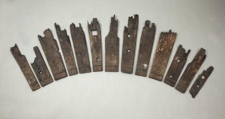 Pojemnik drewniany  Trzynaście klepek beczki o różnych szerokościach. Prawdopodobnie są to części pojemnika wtórnie użytego – wkopanego w ziemię jako proste urządzenie odwadniające. Sugestię taką uzasadnia fakt, że zachowały się tylko dolne partie klepek oraz niewielkie okrągłe otwory, przez które mogła przesączać się woda. Pierwotnie beczka była używana do przechowywania i transportu płynów, gdyż w jednej z klepek jest widoczny prostokątny otwór służący do jej napełniania. W wycięty w dolnej części klepek wątor pierwotnie było wstawione dno. Beczki odwadniające zazwyczaj nie miały den.