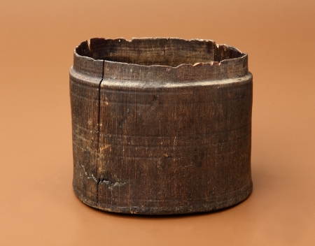 Pojemnik drewniany  Okrągły w rzucie pojemnik wykonano na tokarce. Jego górna część została uformowana w taki sposób, aby osadzona na niej pokrywka nakrywała część ścianki i jednocześnie była dobrze umocowana. Na powierzchni widnieją pasma dookolnych żłobków wykonanych precyzyjnie dzięki mocniejszemu naciskowi noża tokarskiego. Uważa się, że pojemniki tego typu wykorzystywano do przechowywania soli, ziół lub przypraw. Niemal identyczny pochodzi z Lubeki, z warstw datowanych na XIV–XV wiek.