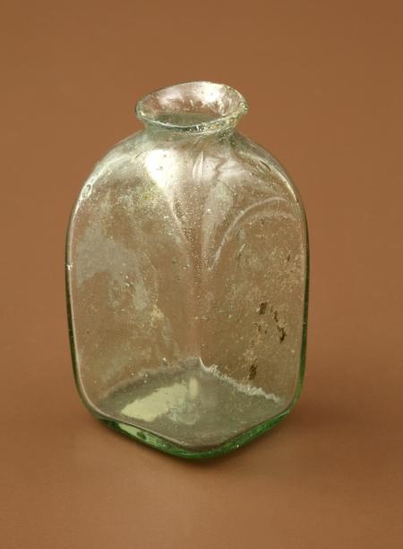 Buteleczka szklana  Należy do typu buteleczek wielobocznych z jednym bokiem wydłużonym, z krótką szyjką i wychylonym wylewem. Została wykonana z zielonego szkła zawierającego pęcherzyki gazowe. Służyła najprawdopodobniej do przechowywania lekarstw lub pachnideł. Znaleziona w zamkowej latrynie użytkowanej od XVI do XVIII wieku.