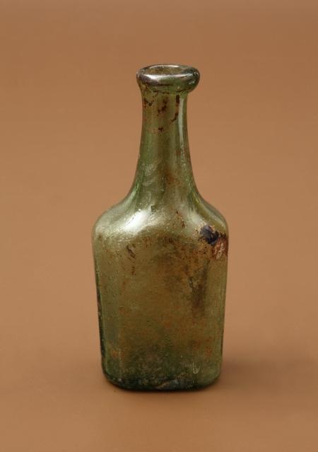 Buteleczka szklana  Należy do typu buteleczek wielobocznych, a ściśle – ośmiobocznych, z jednym bokiem wydłużonym, z wysoką szyjką i zgrubiałym wylewem. Została wykonana z zielonego szkła zawierającego pęcherzyki gazowe. Służyła najprawdopodobniej do przechowywania lekarstw lub pachnideł. Zastosowanie obydwu tych kategorii nie było niegdyś rozróżniane. Ich wytwarzanie i sprzedaż odbywały się w tych samych miejscach, dzisiaj zwanych aptekami – najbliższa zamkowi mieściła się w tym czasie u zbiegu obecnych ulic Grodzkiej i Szewskiej. Ta buteleczka została znaleziona w zamkowej latrynie użytkowanej od XVI do XVIII wieku.