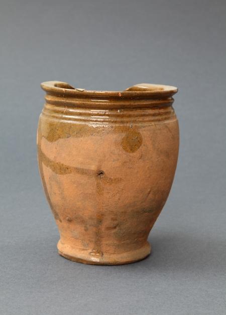 Naczynie ceramiczne – garnek  Lokalny wyrób pomorski, forma charakterystyczna w wyposażeniu kuchni w XVII wieku. Służył do gotowania i przechowywania produktów żywnościowych. Wykonany z gliny o dużej zawartości żelaza, dzięki czemu podczas wypału w piecu garncarskim zyskał specyficzną czerwonawą barwę. Jego wnętrze oraz część zewnętrzną przy wylewie pokryto żółtym szkliwem. Pierwotnie garnek miał taśmowate ucho umożliwiające przenoszenie.