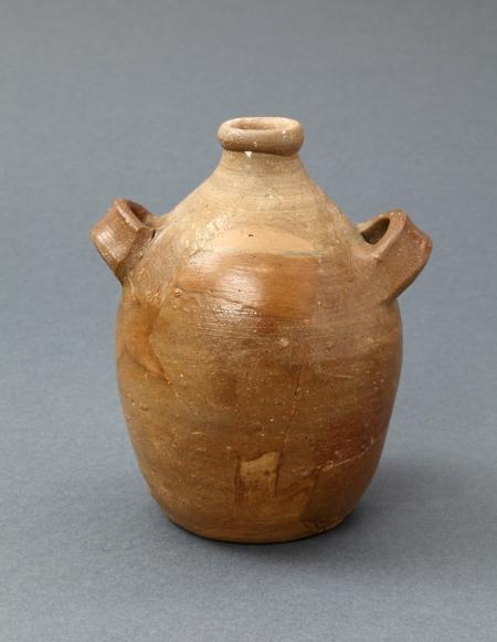 Naczynie ceramiczne – flasza  Naczynie wykonano z kamionki, ceramiki charakteryzującej się bardzo dobrymi parametrami – znaczną twardością i niską przesiąkliwością. Powierzchnia zewnętrzna jest pokryta brązowym szkliwem. Cechą charakterystyczną flasz są dwa poziome ucha umieszczone w górnej partii brzuśca. Naczynia tego typu służące do przechowywania i transportu płynów były użytkowane w 2. połowie XVI – 1. połowie XVII wieku.