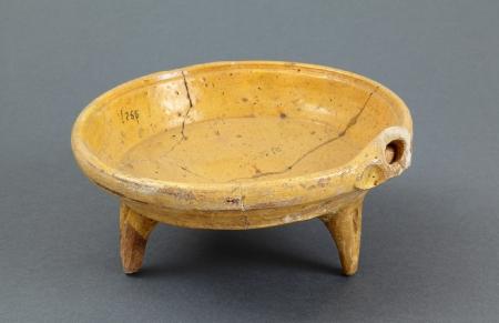 Naczynie ceramiczne – trójnóżek  Kształtem przypomina współczesną patelnię i tak też jest niekiedy określane. Naczynie zaopatrzone w trzy nóżki umożliwiające wstawienie bezpośrednio do ognia i zapewniające stabilność. Przenoszenie ułatwiał drewniany uchwyt wsuwany w rurkowaty otwór widoczny przy ściance. Uważa się, że płaskie trójnóżki służyły do pieczenia i smażenia. Obie strony – wewnętrzna i zewnętrzna – oraz nóżki są pokryte żółtym szkliwem. Patelnie tego typu wytwarzano na Pomorzu od końca XVI przez cały XVII wiek.