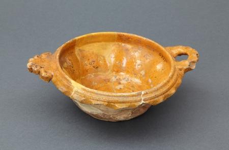 Naczynie ceramiczne – misa  Niewielki egzemplarz wykonany z delikatnej glinki, z efektownym uchwytem w kształcie stylizowanego liścia oraz poziomym, modelowanym uchem umieszczonym po przeciwnej stronie. Brzeg naczynia jest zaopatrzony w ozdobną karbowaną listwę. Wnętrze pokryto jednobarwnym, żółtawym szkliwem. Jest to niewielkie naczynie stołowe lokalnego pochodzenia, wykonane najpewniej w 1. połowie XVII wieku.