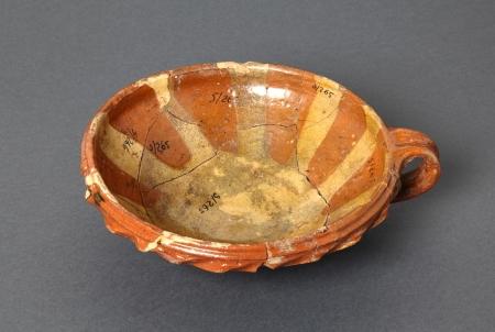 Naczynie ceramiczne – misa  Naczynie to służyło najpewniej do spożywania posiłków. Zostało wykonane z gliny żelazistej wypalonej na kolor czerwony. Powierzchnię wewnętrzną ozdobiono naprzemiennie czerwoną i żółtą polewą dającą efekt rozchylonych płatków kwiatu. Brzeg naczynia jest skierowany pionowo ku górze i od zewnątrz ozdobiony karbowaną, zabarwioną na czerwono listwą. Misę zaopatrzono w jedno pionowe, taśmowate ucho. Jest to wyrób pomorski powstały u schyłku XVI lub w pierwszej połowie XVII wieku.