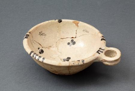 Naczynie ceramiczne  Niewielkie płytkie naczynie zaopatrzone w jedno poziome uszko. Wykonane z jasnej glinki, pokryte od strony wewnętrznej białą polewą, zdobione za pomocą delikatnych czarnych motywów. Jest to lokalny wyrób pomorski z XVI–XVII wieku.