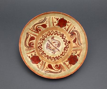 Naczynie ceramiczne – talerz  Głęboki talerz o dużej średnicy wykonano z gliny o dużej zawartości żelaza, która podczas wypału w wysokiej temperaturze nabiera czerwonej barwy. Jego wnętrze jest pokryte wielobarwnym, malowanym ornamentem zawierającym motywy geometryczne w postaci dookolnych linii i pionowych kresek oraz stylizowane motywy roślinne. Zastosowano kolory: żółty, czerwony i zielony. Jest to najpewniej wyrób miejscowych garncarzy okresu nowożytnego.