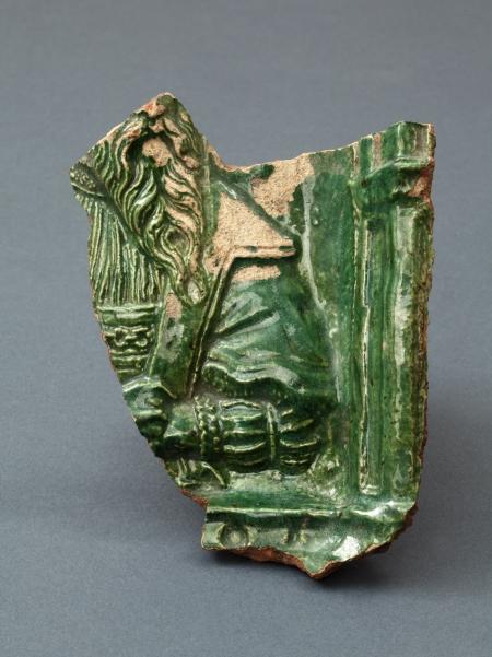 Kafel płytowy  Fragment płyty kafla przedstawiający męskie popiersie z obfitą brodą, w bogatym renesansowym stroju. Fragmentaryczność zachowania nie pozwala jednoznacznie stwierdzić, czy jest to jeden z kafli z wizerunkami władców, jakie znajdowały na piecach wykonanych za czasów Barnima XI, czy to już element nowego wystroju z czasów Jana Fryderyka. Kafel jest pokryty zielonym szkliwem.