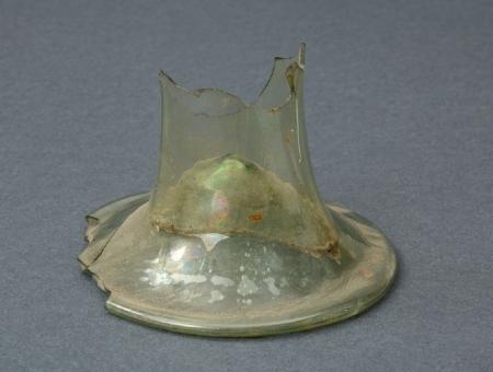 Szklanica  Fragment dolnej części szklanicy typu fletowatego. Naczynia tego typu charakteryzowały się wysoką, wysmukłą czaszą osadzoną na szerokiej, kolistej stopce. Opisywany fragment ma kształt cylindryczny i wklęsłą stopkę. Szklanica została wykonana ze szkła przezroczystego. Nie wiadomo, czy był to egzemplarz zdobiony. Pochodzi z XVII wieku.