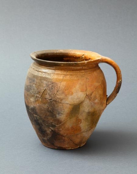 Naczynie ceramiczne – garnek  Gliniane garnki należą do kategorii źródeł najczęściej odkrywanych w nawarstwieniach kulturowych. Naczynia te, niezbędne w kuchni, stosunkowo szybko ulegały zniszczeniu i były zastępowane kolejnymi. Prezentowany egzemplarz ma wyraźnie widoczne okopcenie. Jest zdobiony rzędem stempelków pod szyjką. Tego typu naczynia znane są z okresu od końca XVI do początków XVIII stulecia. Uważa się je za wyroby lokalnych pomorskich warsztatów garncarskich.