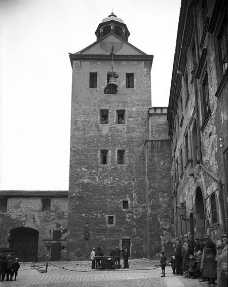 Zamek – dziedziniec menniczy  Widok na wieżę kościoła zamkowego od południa, w czasie wciągania dzwonu, fot. ok. 1925   MNS/A.Foto/4984
