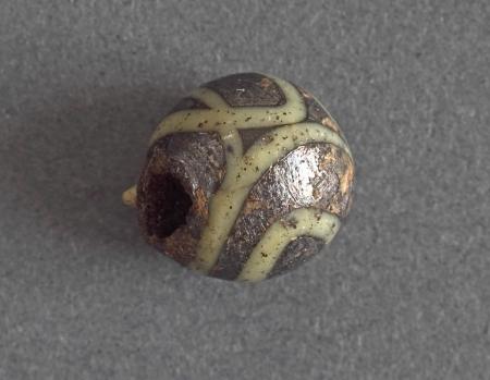Paciorek szklany  Paciorek o kształcie kulistym – część kolii. Został wykonany z nieprzezroczystego fioletowego szkła, w które wtopiono wstęgę żółtego szkliwa. Paciorki były wykonywane różnymi metodami. Najczęściej stosowano tzw. technikę nawijania. Formowanie paciorka tą metodą polega na wyciągnięciu z tygla rozgrzanej masy szklanej i nawinięciu jej na pręt metalowy szybkim ruchem obrotowym. Średnica kanalika paciorka jest równa grubości pręta. W Szczecinie paciorki kuliste występowały już w najstarszych etapach zagospodarowania centralnej części wczesnośredniowiecznego miasta w 2. dekadzie X wieku. Ponownie pojawiły się w warstwach z XII wieku i 1. połowy XIII wieku.
