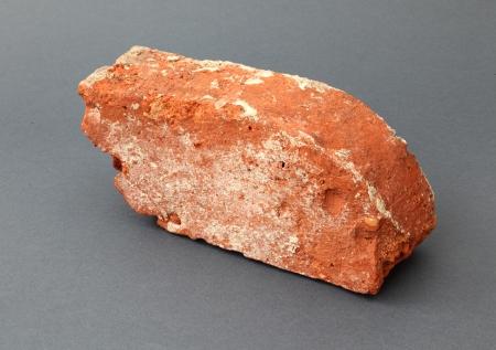 Ceramika budowlana – cegła  W trakcie badań archeologicznych związanych z okrywaniem reliktów architektury murowanej zazwyczaj pozyskuje się duże ilości różnego rodzaju ceramiki budowlanej, przede wszystkim cegieł. Są wśród nich również tzw. kształtki, cegły w szczególny sposób profilowane. Prezentowana cegła jest specyficzną kształtką w tzw. odmianie fazowanej. Tego typu wyroby były używane przy budowie otworów – ościeży wejść i okien. Półkoliście uformowane narożniki kształtek optycznie poszerzały otwory w surowych średniowiecznych murach.