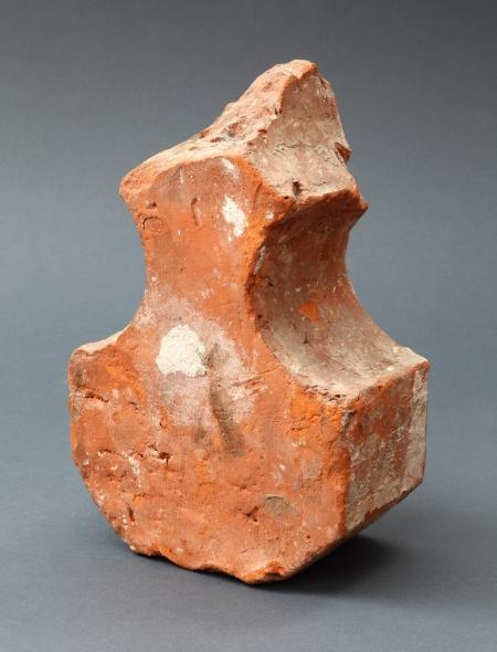 Ceramika budowlana – cegła  Jest to przykład profilowanych cegieł – kształtek, wykonywanych w specjalnych formach, które były wykorzystywane w rozmaitych detalach architektonicznych, na przykład we fryzach. Prezentowana kształtka służyła do wymurowania żeber sklepiennych w tzw. sklepieniu krzyżowym. W architekturze gotyckiej występuje ono w różnych odmianach. Początkowe formy miały wyłącznie znaczenie konstrukcyjne, z czasem w coraz większym stopniu spełniały też funkcję dekoracyjną.
