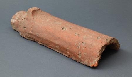 """Ceramika budowlana – dachówka  Na szczecińskim zamku stosunkowo wcześnie, bo już w fazie budowli o konstrukcji ramowo-słupowej, zaczęto stosować ceramiczne pokrycia dachów. Widoczny tutaj element jest specyficzną formą dachówki i nosi nazwę """"gąsior"""". Gąsiory, leżące rzędem jeden za drugim i częściowo na siebie zachodzące, stanowiły zwieńczenie kalenicy (czyli najwyższego miejsca na dachu), nakrywając górne partie najwyższego szeregu leżących poniżej, z obu stron, płaskich dachówek."""