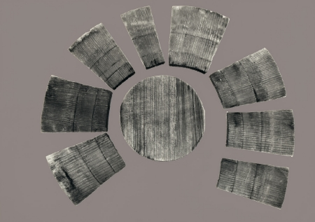 """Drewniana miseczka klepkowa  Naczynie składało się z okrągłego, cienkiego denka i małych trapezowatych klepek. To uformowanie klepek nadało mu kształt donicowaty. Cechą charakterystyczną tego typu naczyń są specjalne schodkowate zaciosy na zewnętrznej powierzchni klepek, służące do oparcia wiklinowych obręczy oraz płytki rowek wątoru przy ich dolnej krawędzi od wnętrza, w który """"wchodziło"""" dno. Miały uniwersalne zastosowanie, w zależności od gabarytów mogły służyć jako naczynia do spożywania pokarmów bądź przechowywania produktów lub jako kubki do picia. Były w powszechnym użyciu na terenie całej Europy od XI do XV wieku, na co wskazują znaleziska archeologiczne."""