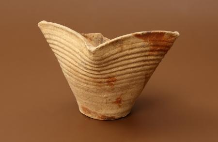 Kafel  Kafle ceramiczne służyły do wykładania powierzchni urządzeń grzewczych – pieców. Były wytwarzane podobnie jak naczynia na kole garncarskim, po uformowaniu wypalano je w piecach i szkliwiono. Początkowo kafle piecowe miały postać garnków z okrągłym otworem, który z czasem zmienił kształt na kwadratowy. Przytwierdzano je do ściany pieca otworem na zewnątrz. Kafle z kwadratowym otworem – tzw. miskowe – były łatwiejsze w montażu. Kafel znaleziony na Wzgórzu Zamkowym nie ma zdobienia, być może piec zbudowany z tego typu kafli służył do ogrzewania jakiegoś mniej reprezentacyjnego pomieszczenia zamku.