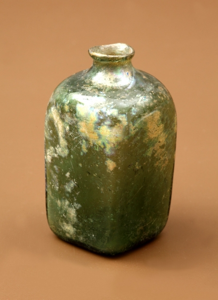 Buteleczka szklana  Ma kształt czworoboczny, w przekroju poprzecznym kwadratowy, krótką szyjkę, krawędź wylewu jest wychylona na zewnątrz. Dno jest wklęsłe ze śladem oderwania  przylepiaka. Do jej wyrobu użyto seledynowego szkła zawierającego pęcherzyki gazowe (świadczące o niskim poziomie technologicznym wytwórcy szkła). Należy do grupy niewielkich buteleczek służących do przechowywania lekarstw lub pachnideł. Okazy tego typu są powszechnie znane od połowy XVI wieku, choć prawdopodobnie wytwarzano je już wcześniej, na co wskazują znaleziska z Drezna, z obiektów datowanych nawet na 1. połowę XIII wieku. Szczecińską buteleczkę można datować najwcześniej na schyłek XVI lub 1. połowę XVII stulecia.
