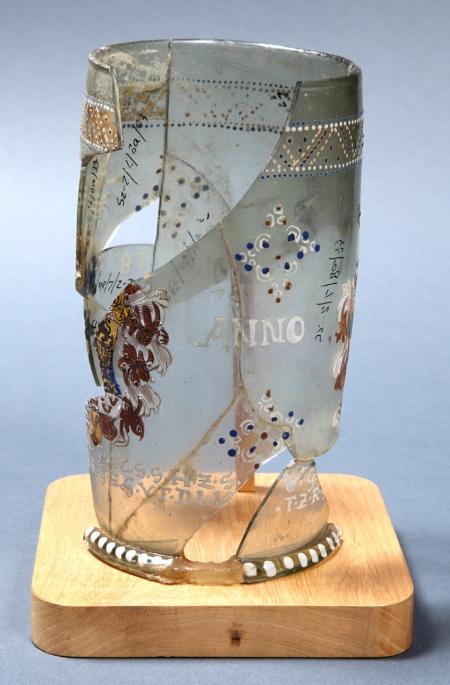 """Szklanica  Bogato zdobiona szklanica o formie cylindrycznej, nieznacznie wybrzuszonej, z dnem wklęsłym ze śladem przylepiaka (ślad oderwania rury, za pomocą której wydmuchiwano przedmiot), z dolepioną profilowaną stopką dekorowaną białymi punktami. Zastała ozdobiona dwoma tarczami herbowymi. Pierwszą z nich, należącą do książąt pomorskich, podtrzymują fantazyjnie ubrane postacie; drugą, wiążącą się z elektorami saskimi, wieńczą hełmy z pióropuszami. Na szklanicy widnieją też napisy: data """"ANNO 1618"""" i wypisana dużymi literami tytulatura pary książęcej – księcia Franciszka I i jego żony Zofii, córki elektora saskiego Krystiana. Szklanica pełniła funkcję wilkomu, tj. naczynia służącego do spełniania toastów przy szczególnych wydarzeniach. Tą okazją wydają się w tym przypadku uroczystości związane z objęciem władzy w Szczecinie przez Franciszka I, co miało miejsce właśnie w 1618 roku."""