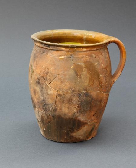 Naczynie ceramiczne – garnek z uchem  Zgodnie z powszechnym rozumieniem garnki ceramiczne służyły do przygotowywania i przechowywania pokarmów. Tego typu naczynia, jak prezentowane powyżej, należały do podstawowego wyposażenia kuchni od końca XVI do początków XVIII wieku. Były produkowane na Pomorzu, w lokalnych warsztatach garncarskich. Naczynie wykonano z wypalonej gliny. Powierzchnię wewnętrzną pokryto żółtym szkliwem zapobiegającym wsiąkaniu płynów w czerep. Rozchylenie krawędzi otworu umożliwiało nakrywanie naczynia obwiązywaną wokół tkaniną.