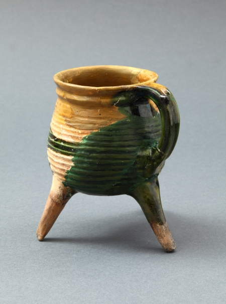 Naczynie ceramiczne – trójnóżek-rondel  Prezentowany rondel wyróżnia wysokość nóżek i dwukolorowe – żółte i zielone szkliwienie powierzchni zewnętrznej. Wnętrze naczynia jest żółte. Uważa się, że naczynia tego typu służyły do sporządzania naparów i były ustawiane bezpośrednio w palenisku. Użytkowano je w XVII wieku.