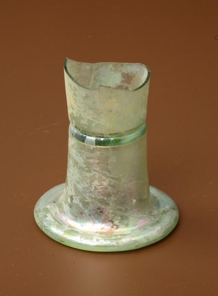 Szklanica  Fragment dolnej części szklanicy typu fletowatego, który charakteryzuje się wysoką, prostą czasza przechodząca w okrągłą, wklęsłą stopkę. Wykonano ją z bezbarwnego szkła. Powierzchnię pokrywa delikatna warstewka opalizującej patyny. Została ozdobiona prostą taśmą szklaną. Flety, gdzie taśmy szklane są karbowane, datuje się na XVII wiek.