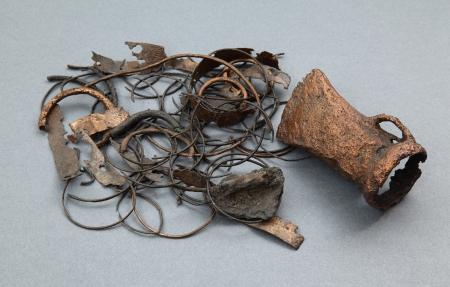 Skarb przedmiotów wykonanych z brązu  Został znaleziony w 1973 roku podczas prac związanych z odbudową zamku na dziedzińcu głównym. Składają się na niego całe przedmioty, jak siekierka z tulejką (do mocowania drewnianego styliska) i uszkiem, pięć kółek o różnej wielkości oraz spirala, jak również złom i surowiec: fragmenty taśmowej bransolety spiralnej zdobionej zygzakiem z tłoczonych punktów, ułamki naczynia, naszyjnika skośnie żłobkowanego, drugiej siekierki, taśmy i kółka. Wszystkie brązy były umieszczone w glinianym naczyniu. Skarb jest datowany na początek epoki żelaza, kiedy na Wzgórzu Zamkowym istniał gród ludności kultury łużyckiej. Jego mieszkańcy parali się odlewnictwem brązu, co poświadcza forma odlewnicza znaleziona w pobliskiej ziemiance.