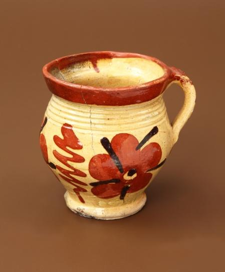 Naczynie ceramiczne – kubek  Kubki należą do zastawy stołowej i służyły do picia. Ten egzemplarz jest zdobiony malowanym ornamentem florystycznym – motywami kwietnymi rozdzielanymi barwnymi zygzakami. Taśmowate ucho doklejone do krawędzi wylewu, także zdobione malowanymi elementami, ułatwiało przenoszenie i przechylanie naczynia. Czerwoną dekorację ożywioną czarnymi akcentami umieszczono na żółtym podkładzie. Żółtą barwę ma także wnętrze kubka.