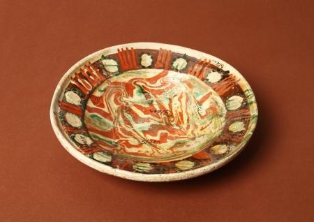 Naczynie ceramiczne – talerz  Talerz wykonany z białej glinki od strony wewnętrznej jest bardzo bogato zdobiony za pomocą wielobarwnej polewy pokrytej szkliwem. Całe dno pokrywają żółto-brązowo-zielone esy-floresy, przy krawędzi zaś zdobienie ma postać szerokiego, brązowego pasa z żółtymi plamami umieszczonymi w polach wydzielonych pionowymi, czerwonymi, potrójnymi kreskami. Jest to typ talerza głębokiego wchodzący w skład nowożytnej zastawy stołowej wyprodukowany na Pomorzu lub w Meklemburgii.