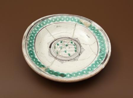 """Naczynie ceramiczne – talerz  Głęboki talerz stanowiący element zastawy stołowej jest wyrobem miejscowym, wykonanym na Pomorzu. Wykonano go z żółtej glinki. Od strony wewnętrznej jest pokryty białym szkliwem z zielono-czarnym, malowanym ornamentem w postaci dookolnych pierścieni. W centralnej części dna, w szarym promienistym otoku, znajduje się sentencja dewocyjna: """"Mein Gott, nun ist es wieder Morgen"""" [Mój Boże, teraz ponownie jest ranek]. Tekst został zaczerpnięty modlitewnika szkolnego z XVIII wieku. Identyczny talerz znaleziono w Kamieniu Pomorskim."""