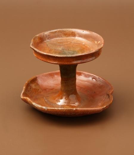 """Wyrób ceramiczny – świecznik  Został wykonany z glinki żelazistej wypalającej się na kolor czerwonobrązowy. Składa się z dwóch kolistych, płytkich miseczek połączonych walcowatym trzonem. Świeczniki zazwyczaj były wykorzystywane do mocowania świec oświetlających pomieszczenia. W tym przypadku prawdopodobnie było możliwe także użycie knota zanurzonego w oliwie. Najpewniej do osadzenia knota służyły niewielkie """"dziubki"""", które są uformowane na krawędziach."""