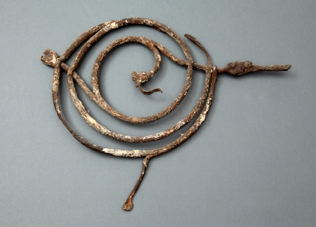 Ozdoba żelazna  Fragment ozdoby. Metaloplastyka wykonana z żelaza w postaci spirali wzbogaconej o motyw liścia lub pióropusza. Mogła mieć zastosowanie jako ozdobna krata montowana w oknach czy drzwiach. Prawdopodobnie pochodzi ze skrzydła menniczego zamku.