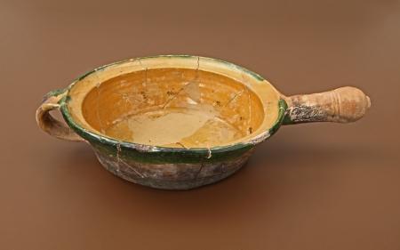 Naczynie ceramiczne – patelnia  Patelnia ceramiczna, podobnie jak dzisiejsze egzemplarze metalowe, służyła do smażenia i pieczenia potraw. To naczynie jest pozbawione nóżek umożliwiających ustawianie bezpośrednio w ogniu. Prawdopodobnie było umieszczane na żelaznej podstawce wstawianej do paleniska. Potwierdzeniem są wyraźnie widoczne okopcenia. Zarówno duży rozmiar, jak i związany z tym ciężar spowodowały konieczność zaopatrzenia patelni w rurkowaty, gliniany uchwyt oraz dodatkowo w duże, taśmowate ucho. Całe naczynie było barwione i szkliwione, przy czym strona wewnętrzna jest żółta, zewnętrzna – zielona. Patelnię można datować na XVII stulecie.