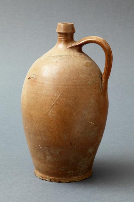 Naczynie ceramiczne – flasza  Baniasta flasza kamionkowa, służąca do przechowywania i transportu płynów, ma niewielką szyjkę i wąski wylew. Jest zaopatrzona w ucho ułatwiające przechylanie i przenoszenie. Brązową barwę nadała jej polewa tzw. solna.